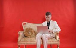 Ritratto di giovane vestito bianco d'uso teenager e di seduta dell'ufficio dell'uomo sul sofà di lusso dorato su fondo rosso lavo fotografia stock
