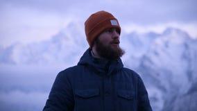 Ritratto di giovane viaggiatore maschio barbuto nella penombra nelle montagne Stare pensante e sorridente per ragionare stock footage