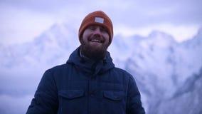 Ritratto di giovane viaggiatore maschio barbuto nella penombra nelle montagne Stare pensante e sorridente per ragionare video d archivio
