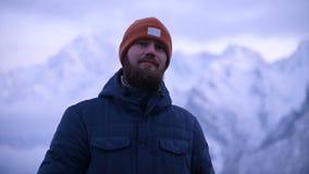 Ritratto di giovane viaggiatore maschio barbuto nella penombra nelle montagne Stare pensante e sorridente per ragionare archivi video