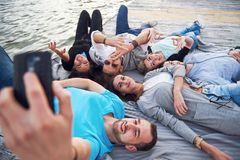 Ritratto di giovani amici felici sul pilastro nel lago Mentre godendo del giorno e facendo selfie Immagine Stock Libera da Diritti