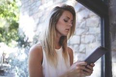 Ritratto di giovani belle donne bionde che leggono libro elettronico sulla sua compressa digitale mentre stando vicino alla grand Immagine Stock