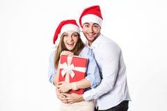 Ritratto di giovani coppie attraenti in cappelli di Santa con il regalo su fondo bianco Immagini Stock