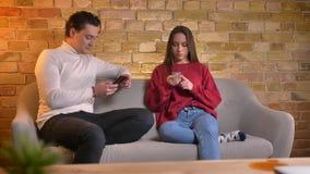 Ritratto di giovani coppie caucasiche che si siedono sul sofà e che scrivono sugli smartphones in atmosfera domestica video d archivio