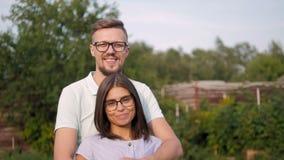 Ritratto di giovani coppie felici amorose nel giardino, uomo che abbraccia la sua moglie video d archivio