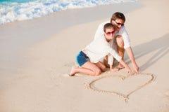 Ritratto di giovani coppie felici che dissipano un cuore sopra Fotografia Stock Libera da Diritti