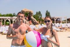 Ritratto di giovani coppie sulla spiaggia con beach ball Fotografia Stock Libera da Diritti