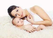 Ritratto di giovani madre felice e del bambino che si trovano sul letto Fotografie Stock Libere da Diritti