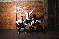 Ritratto di giovani musicisti d'avanguardia sopra un muro di mattoni Immagini Stock Libere da Diritti