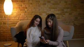 Ritratto di giovani ragazze caucasiche che si siedono sul pavimento e che fanno le selfie-foto allegre facendo uso dello smartpho stock footage