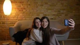 Ritratto di giovani ragazze caucasiche che si siedono sul pavimento e che fanno le selfie-foto graziose facendo uso dello smartph stock footage