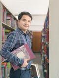 Ritratto di giovani sorriso e supporto dello studente con il libro Immagine Stock Libera da Diritti