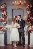 Ritratto di giovani sposa e sposo felici in un interno classico vicino al camino con i fiori Giorno delle nozze, tema di amore Pr immagine stock
