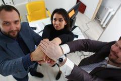 Ritratto di giovani uomini d'affari allegri nel posto dell'ufficio le loro mani una sopra l'altra immagine stock