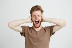 Ritratto di grida gridanti di chiusura delle orecchie del giovane uomo arrabbiato emotivo sopra il fondo bianco Fotografia Stock