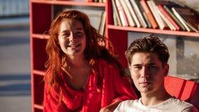 Ritratto di Guy On The Wheelchair Says qualcosa alla ragazza ed alla lei dai capelli rossi Iistens con attenzione, su passeggiata fotografie stock