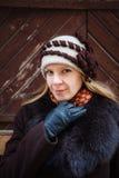 Ritratto di inverno della giovane donna con il cappello, il cappotto marrone ed i guanti di cuoio neri, all'aperto Fotografia Stock