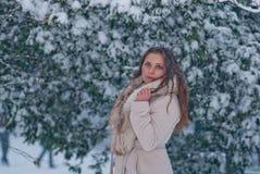 Ritratto di inverno di una donna in camice durante le precipitazioni nevose in un parco Fotografia Stock
