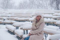 Ritratto di inverno di una donna in camice durante le precipitazioni nevose in un parco Immagini Stock