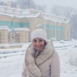 Ritratto di inverno di una donna in camice durante le precipitazioni nevose in un parco Fotografie Stock