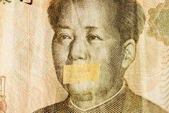 Ritratto di Mao, capo della Cina con la bocca chiusa su una banconota degli yuan cinesi, come simbolo dell'instabilità di economi fotografia stock libera da diritti