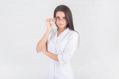 Ritratto di medico della donna al corridoio dell'ospedale, tenendo il computer della compressa, esaminando macchina fotografica,  Immagine Stock