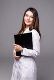 Ritratto di medico femminile allegro con la lavagna per appunti, isolato sopra fondo bianco fotografie stock