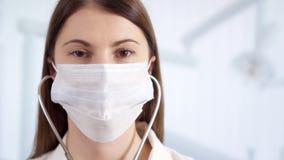 Ritratto di medico femminile professionista nella maschera che sta nella stanza di ospedale Medico della donna con lo stetoscopio archivi video