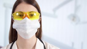 Ritratto di medico femminile professionista nella maschera che sta nella stanza di ospedale Medico della donna sul lavoro video d archivio