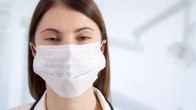 Ritratto di medico femminile professionista nella maschera che sta nella stanza di ospedale Medico della donna sul lavoro stock footage