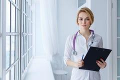 Ritratto di medico femminile serio con la lavagna per appunti Immagine Stock