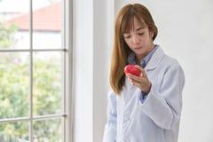Ritratto di medico femminile sorridente con cuore rosso Medico amichevole della giovane donna con cuore rosso a disposizione Fuoc fotografia stock
