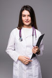 Ritratto di medico grazioso felice della giovane donna con la lavagna per appunti e lo stetoscopio sopra fondo bianco Immagini Stock Libere da Diritti