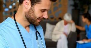 Ritratto di medico maschio che per mezzo della compressa digitale archivi video