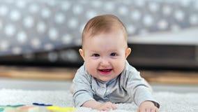 Ritratto di menzogne sorridente del piccolo bambino sveglio adorabile sul tappeto lanuginoso a casa che esamina macchina fotograf archivi video