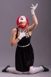 Ritratto di mimo femminile con il cappello rosso ed il bianco Fotografie Stock