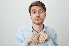 Ritratto di di modello maschio europeo attraente sveglio facendo espressione innocente e tenera, le sopracciglia di sollevamento  immagini stock libere da diritti