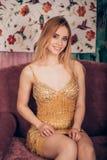 Ritratto di modo di una donna bionda splendida che porta un breve vestito dorato brillante e che esamina la macchina fotografica  immagine stock