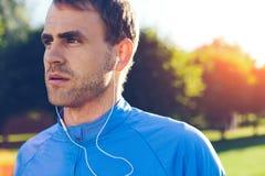 Ritratto di musica d'ascolto dell'atleta prima dell'allenamento nel parco Immagini Stock