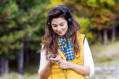 Ritratto di musica d'ascolto della bella giovane donna all'aperto Godere della musica Fotografia Stock