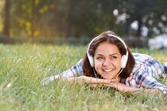 Ritratto di musica d'ascolto della ragazza che si trova all'erba Fotografia Stock