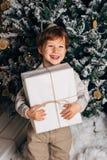 Ritratto di Natale di un'atmosfera accogliente del giovane ragazzo intorno all'albero di Natale Bambino sveglio che tiene il cont Fotografia Stock