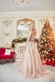 Ritratto di Natale di una ragazza in un vestito festivo brillante sui precedenti della decorazione di Natale nell'interno elegant immagini stock libere da diritti
