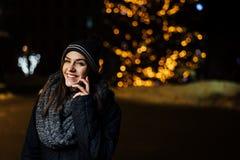 Ritratto di notte di bella donna castana che utilizza smartphone durante l'inverno freddo nel parco Gioia di inverno Vacanze inve immagine stock libera da diritti