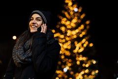 Ritratto di notte di bella donna castana che utilizza smartphone durante l'inverno freddo nel parco Gioia di inverno Vacanze inve fotografia stock libera da diritti