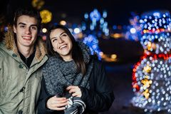 Ritratto di notte di una coppia felice che sorride godendo dei aoutdoors della neve e di inverno Gioia di inverno Emozioni positi fotografia stock libera da diritti