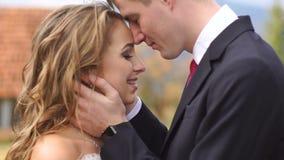 Ritratto di nozze romantico Lo sposo bello sta baciando morbidamente la sua sposa sorridente incantante nella testa all'aperto archivi video