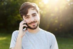 Ritratto di Outdoot dell'uomo barbuto felice con la pettinatura alla moda che ha conversazione telefonica con la sua amica mentre fotografie stock libere da diritti