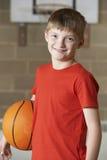 Ritratto di pallacanestro della tenuta del ragazzo nella palestra della scuola immagine stock