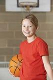 Ritratto di pallacanestro della tenuta della ragazza nella palestra della scuola fotografia stock